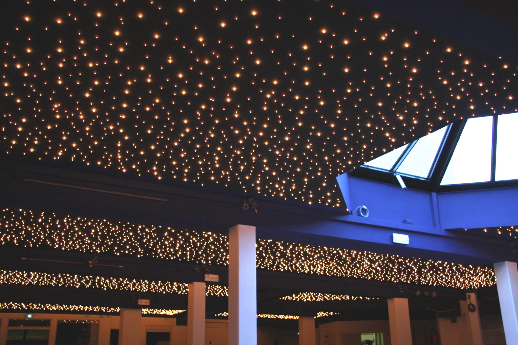 Starlit ceiling, 15 000 stars-LEDs, 400m2, Seven Spirits, Paris / For the owner of a Parisian ballroom, Semeur d'Étoiles designed and installed the largest European starlit ceiling. Despite the room's network of beams, we succeeded in creating a ceiling that preserved the room's high ceilings and added acoustic attenuation. We used a combination of different LED intensities to create the feeling of depth. The starlit ceiling has become the main attraction of the ballroom, allowing the owner a rapid return on his investment.