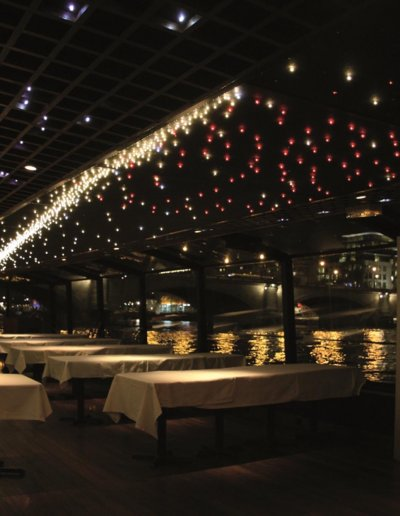 Starlit ceiling on a riverboat on the Seine, LEDs in warm white, pure white and red (static and sparkling), 30x1,5m, Marina de Paris, Paris / The owner of a Parisian riverboat cruise company wished to create an unforgettable setting in which to welcome guests aboard. Many technical constraints made this project challenging: humidity, vibration, temperature, noise, the difference in light quality during the day and at night, access to the power supply, and work while the boats continued to be on service. Nevertheless, Semeur d'Étoiles was able to design and fabricate lighting that enhances the elegant lines of the boats.